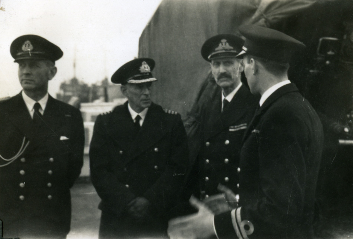 """Album Glaisdale H.Nor.M.S. """"Glaisdale"""". Fotograf: Itn.Knudtzon. En av offiserene på skipet snakker med kongen."""