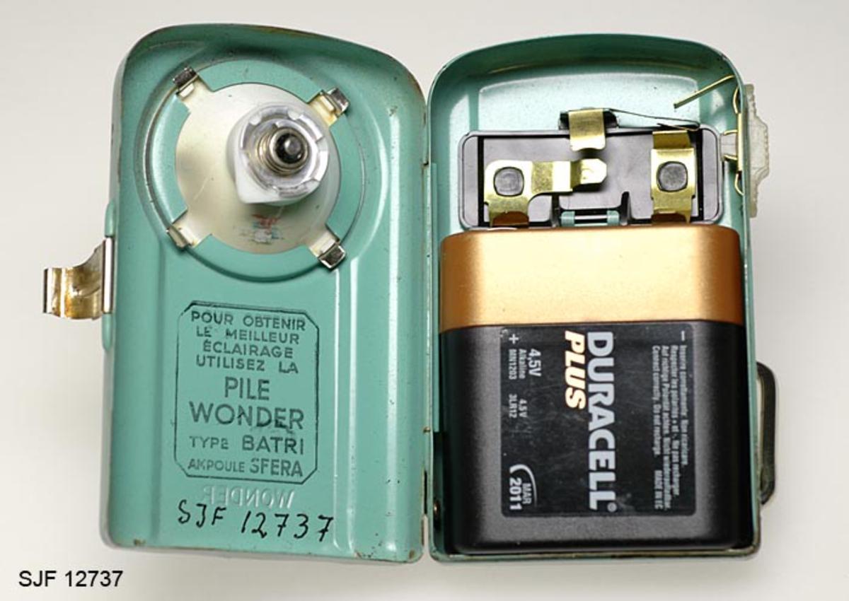 Batteridrevet lommelykt i lakkert metall. Lykta har metallbøyle (støtte) nederst og -hempe øverst. Den er i brukbar stand og ble levert med batteri (Duracell Plus, 4, 5V) som har varighet til mars 2011.