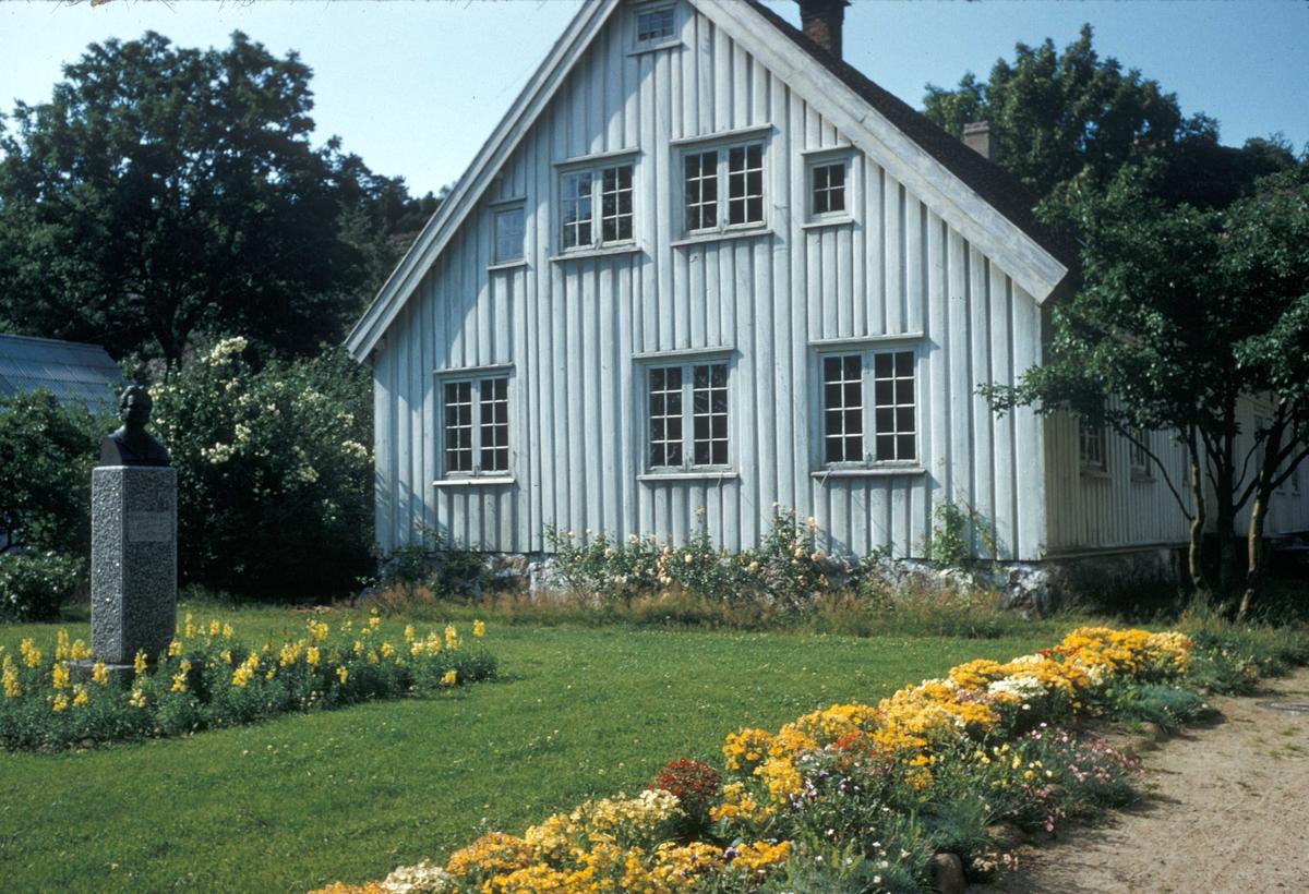 Eksteriøret på Søgne prestegård. Byste av Bjørnstjerne Bjørnson i hagen.