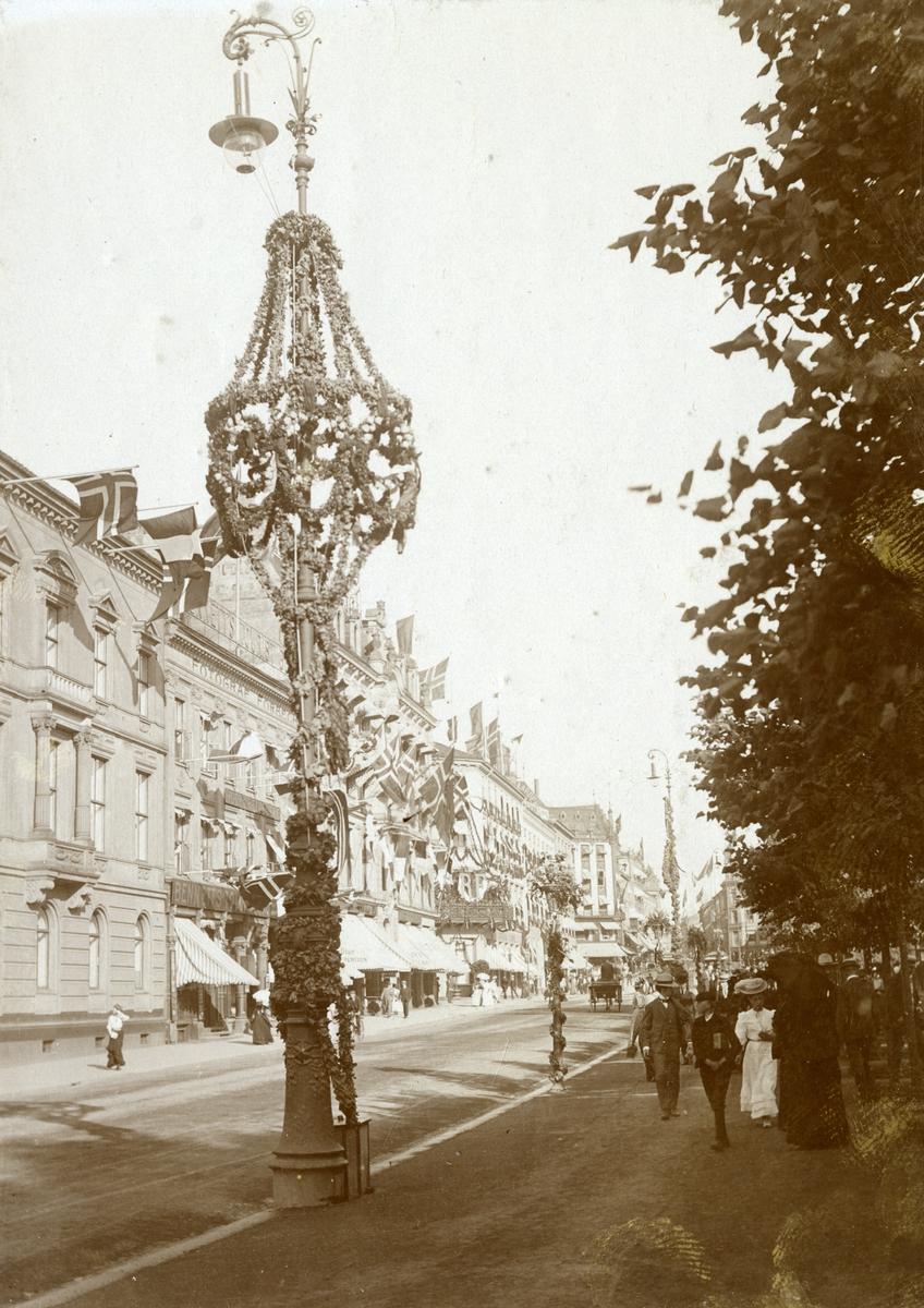 Serie med fire foto fra den franske prsidenten Clement Armand Fallières statsbesøk i Kristiania i 1908. Velkomstpaviljong med baldakin, pyntet med girlander og flagg. Dekorasjoner utført av B. Lange, antakelig. Tilskuere på Honnørbrygga i hovedstaden. Karl Johans gate er også pynytet med dekorasjoner.