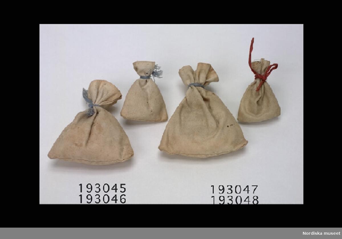 Inventering Sesam 1996-1999: H  5,5  cm Säck av ofärgad bomull, handsydd, fylld med papper, omknuten med blått band. Tillhör dockskåp inv 192.991. Birgitta Martinius 1996