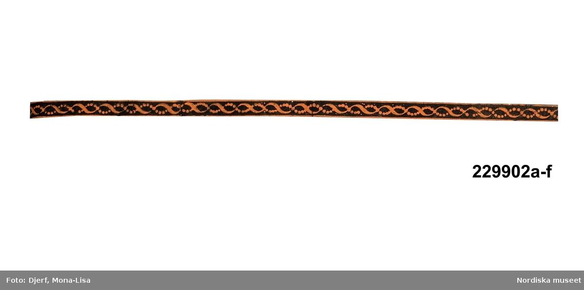 """Huvudliggaren: """"a-f Tapetbård, 6 st., papper med tryckt dekor, terracottafärgad dubbelslinga (band i pärlor) på svart botten, (avklippt kantlist på bred bård.) Br. 1, 5 cm. Ingår i en samling tapeter, som sedan långt tillbaka förvarats i museet.""""  Utdrag ur bilaga: """"Bilaga till inv nr 229.401 - 230.099 Ovanstående tapetbårder är införda i huvudliggaren med proveniensuppgift att de sedan länge förvarats i Nordiska museet. I flera andra källor har de hänförts till Carl Fredrik Torsselius och hans verkstad i Stockholm och dateras till omkring 1820. Alla tapeter är inte tillverkade av Torsselius, utan några av dem är franska ...""""  Katalogkort: """" Tryckt dekor på papper. H 1,5 cm. Fond svart, terracotta.""""  a) Originalrullning, invikt kant. b) Anm.: Fläckvisa mindre färgbortfall. c) Bläckpåskrfit på baksidan """"26 alnar"""" samt del av stämplad namnteckning C. F. Torsselius inom oval, dubbel ram. d) Del av stämplad namnteckning C. F. Torsselius inom oval, dubbel ram. e) Bläckpåskrift på baksidan """"12..."""" samt mycket liten del av stämplad namnteckning C. F. Torsselius inom oval, dubbel ram. f) Del av stämplad namnteckning C. F. Torsselius inom oval, dubbel ram. /Marie Tornehave 2008-04-15"""