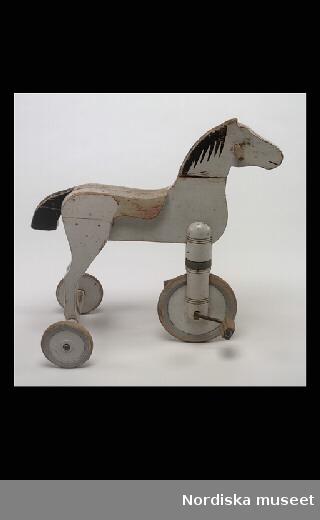 Inventering Sesam 1996-1999: L  60  B  32  H 56  (cm) Trehjuling, cykelhäst, av trä, vit målad, vridbart huvud med handtag, svartmålad man och mun, röd sadel, svart svans, ett hjul framtill med trampor, två baktill. Färgen sliten, ögon sekundärt målade. Saknar märkning sannolikt tillverkad vid Gemla leksaksfabrik, Diö. Birgitta Martinius 1998