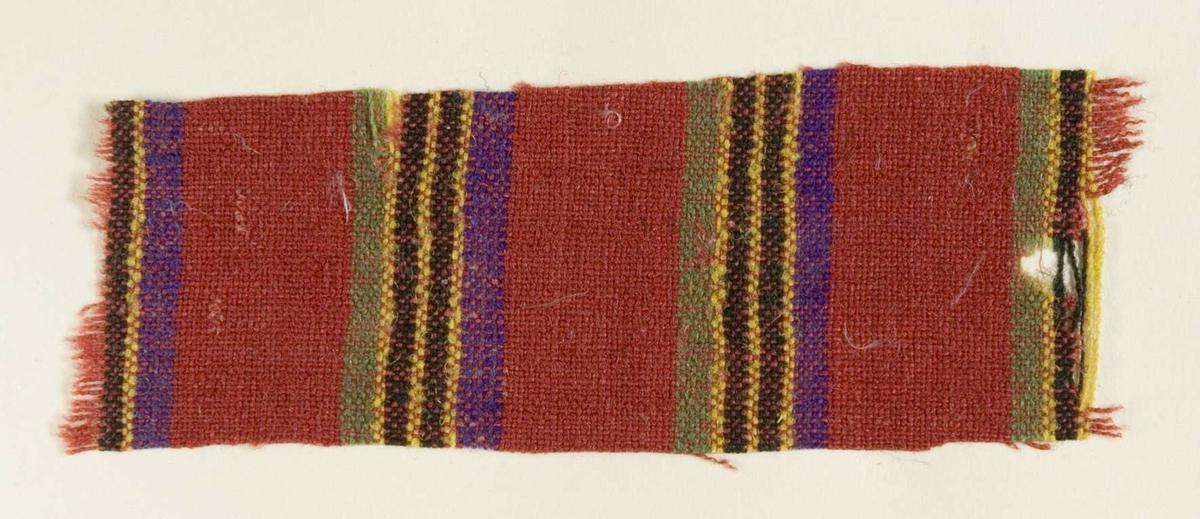 """Vävprov ämnat för kjoltyg i ull- och bomullsgarn, tuskaft. Randigt i rött, violett, gult och grönt. Vävprovet är uppklistrat på en kartong i storleken 22 x 28 cm. I övre högra hörnet finns en stämpel """"Uppsala läns hemslöjdsförening"""" och ett handskrivet nummer, """"A.1607""""."""