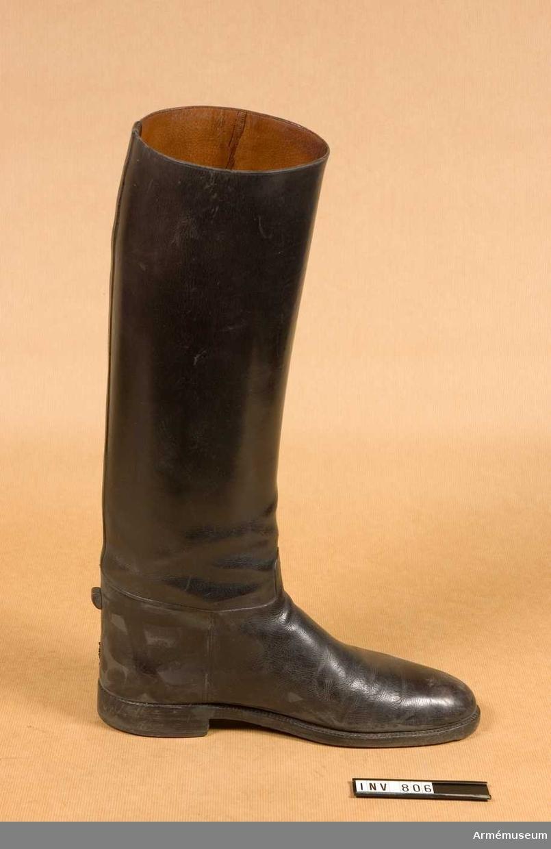 Att bäras till uniform m/1939. Tillåten modell. Höga skaft med söm mitt bak, täckt av en strimma av det skinn som kommer skuren från foten. Foten går från vristen med söm på båda sidor och skuren med en tunga mitt fram. Sulan är randsydd, försedd med tåjärn. Klacken är klackad med hårdgummi eller plast ? kallad neolite. En stopper mitt bak på skon för fasthållande av stigbygel. Invändigt är stöveln klädd med ljust läder.