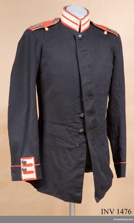"""Stl 50. Av fin kläde, enkelradig med åtta knappar; den nedersta  saknas. Knapparna är helt släta m/1810?. På baksidan märkta """"M Pettersson Stockholm"""". Avskuren midja med fasonerade  insticksfickor bak, kantade med röd passpoal. Ficklocken har tre  knappar. Kragen, 50 mm hög, är röd med """"knapphål"""" av vitt  redgarn. Röda axelklaffar fasta i ärmsömmen. Kantade med  studentsnodd i blått/gult. Oscar II:s namnchiffer i silver.  Knäppta vid rocken med knapp av nickel. För fastsättning av  epålett finns vit träns med röd matta mitt på axeln, på tvären. Matelassérat svart foder. Ljust foder i ärmarna. Innerfickor. Rocken har tillh. konstnär G Hallström, född 1875."""