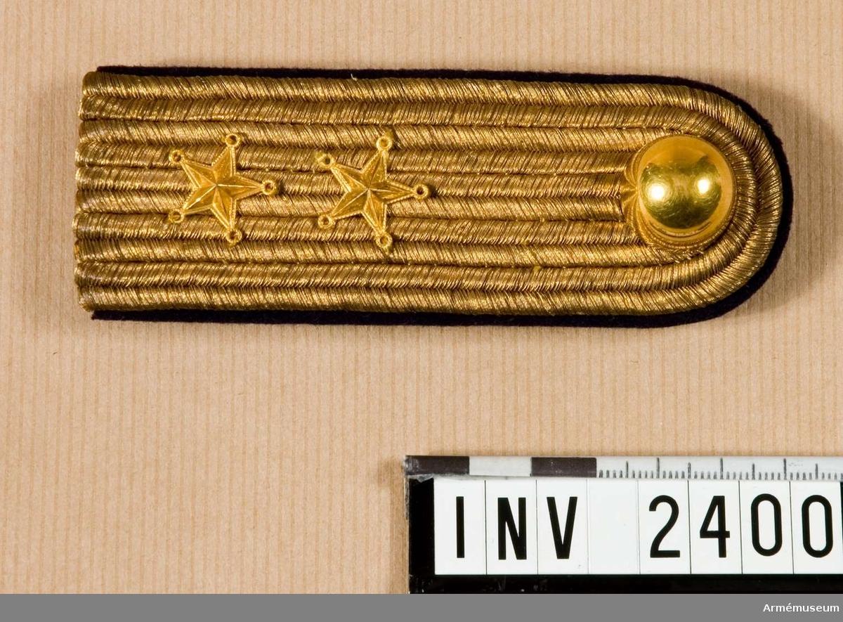 Längd 120 mm. Bredd 45 mm.Fem rader guldgalon tätt bredvid varandra bildar överdelen av axelklaffen. Försedd med knapp m/1901 för Karlskrona grenadjärregemente. Foder och hank av mörkblått kläde. Hake av gulmetall märkt: Holts Gulddrageri Stockholm. Två guldstjärnor som gradbeteckning = löjtnant. Gott skick.