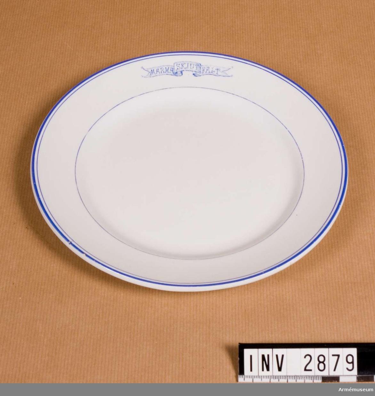 """Vitt porslin med blå dekor; runt ytterkanten en något kraftigare rand än den innanför. Emblem i form av banderoll med text """"MARMA SKJUTFÄLT"""". Undersidan märkt """"Gustavsberg Granit 502 B6 0"""". Har använts vid off.mässen, Marma läger. Porslinet har tillh. A 1 och har förmodligen anskaffats i början av 1930-talet som ersättning för porslin som blev förstört när mässen brann ner feb 1930.  Samhörande nr är 2625-2630, 2876-2881 (2876-2881)."""