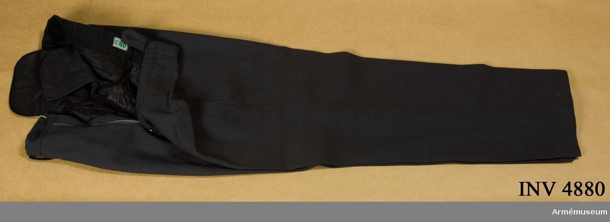 Storlek: C 50. Långbyxor m/1960, menig, I 1. Tillverkade av stålgrå  ripsdiagonal - 65% ull och 36% polyester. Är utan uppslag, har  två raka sidfickor och två bakfickor samt hällor för bälte.UNIA 1977 6:12-13 a.
