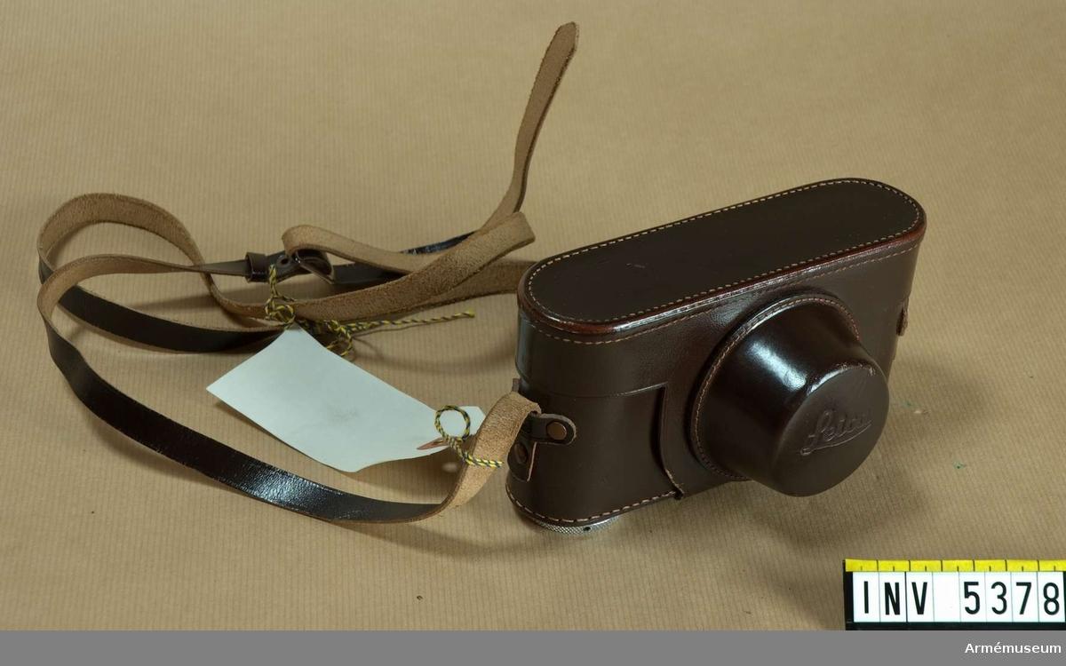 Samhörande nr är 5377, kamera. Väska M 7080-6002 f kamera 151, Leica. Beredskapsväska av brunt läder för Leica kamera äldre än modell III g. Detta syns genom att väskan saknar urtag på baksidan för  betraktande av skalan för inställning av filmkänslighet som  finns på denna kamera. Remmen är mörkt brun. Halkskydd är påträtt, märkt med E Leitz Wetzlar Made in Germany . Gummimaterialet i detta har  blivit sprött och har gått sönder.Tillhör fotomaterielsats 7, låda 3.