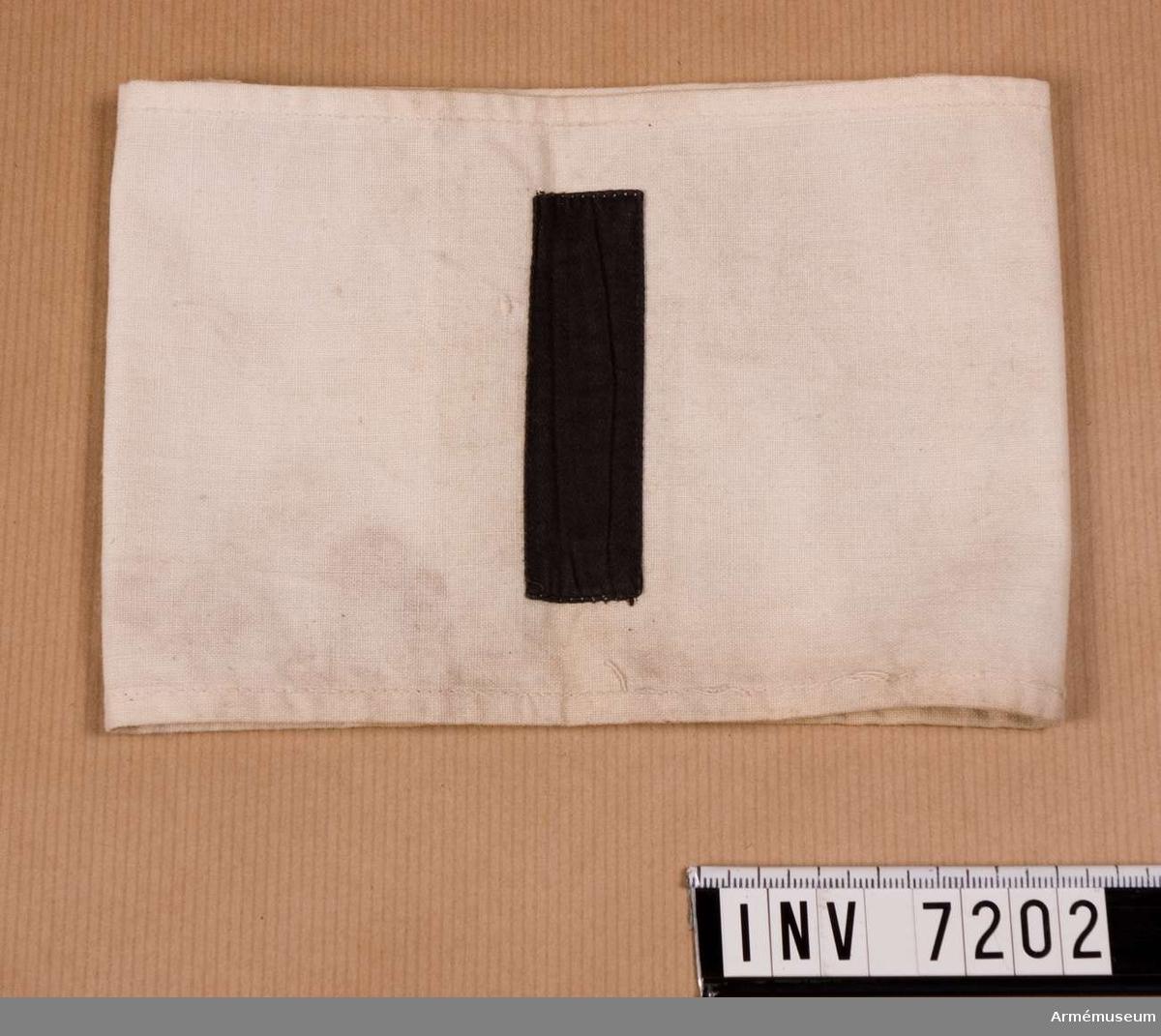"""Av vit bomullsväv, maskinsydd med på mitten en svart i tyg påsydd etta. Mått 20 x 75 mm. Har varit i Bernadottesalen och borttagen därifrån 1982. Svenska brigaden. I finska inbördeskriget 1918 en av svenska frivilliga militärer och civila bildad trupp på 300-400 man, som med utmärkelsen deltog på """"de hvites"""" sida bla i erövringen av Tammerfors (mars - april).  Samhörande nr är 7202 - 7210."""