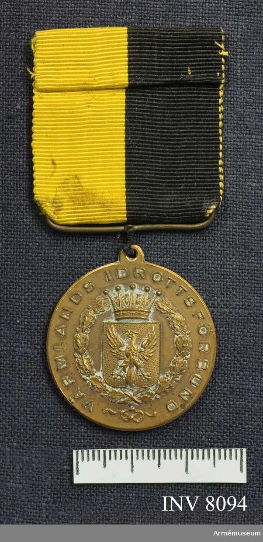 Samhörande AM 8076-. Diameter 30 mm. Tjocklek 2 mm. Vikt 25 g. Färg brons (kopparbrun). I relief på åtsidan (adversen) i mitten Värmlands vapen och i kanten står det: Värmlands idrottsförening. Frånsidan (reversen) är ograverad, har endast lagerkransen i kanten. Medaljen hänger i ett svart och gult ripsband 35 x 35 mm.