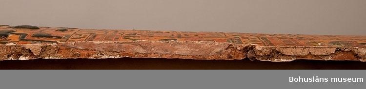 Antropoid mumiebräda dekorerad i flera färger på en gul bakgrund. Brädan lades på mumien inne i kistan. Brädan avbildar den avlidne bärandes en peruk och under hakan finns idag ett hål där ett lösskägg (?) suttit. Ett halsband är avbildat på den övre delen av bröstkorgen där även de korslagda händerna kommer fram. På kroppens mittdel finns två horisontella band med guden Amun-Ra avbildad samt hieroglyfer. Dessa två band åtskiljs av den bevingade himmelsgudinnan Nut. På brädans nederdel fyra horisontella band med gudar och hieroglyfer.  Inscription 1 Htp-di-nsw in Wsir, Xnty Imntt, Wn-nfr, HkA anxw, nTr aA, Hr-ib AbDw, aA, xa m Atf.f, di.f prt-xrw t, Hnkt, kAw, Apdw, xt nbt nfrt abt, Wsir it-nTr, TAy bsnt n Imn [---]. Offering that the king gives to Osiris the foremost of the West, Uennefer, the sovereign of the living ones, the great god, who is in Abydos, the great one, who rises in his atefcrown, so that he may give invocations-offerings in bread and beer, meat and fowl, and all things good and neat to the Osiris, divine father, the chiseler of (the temple) of Amun (---).  Inscription 2 Htp-di-nsw in Ra-HrAxty-tm, Xnty Hwt-aA, bA n pt Hr-ib Axt, s.HD tAwy m wbAt itn.f, di.f pr bA[.i] mAA itn, Wsir it-nTr n Imn, TAy [---]. Offering that the king gives to Re-Horakhty-Atum, the foremost of the Great Temple, who's ba is in heaven, over the horizon, he illuminates the Two Lands, in the opening of his disk, so that (my) ba goes forth and may see the sun disk (Aten), the Osiris, divine father of Amun, the chiseler (---).  Inscription 3 imAxy xr The venerable one before (…).  Inscription 4 imAxy xr Wsir, Xnty The venerable one, before Osiris, the foremost.  Inscription 5 imAxy xr The venerable one (…).  Inscription 6 imAxy xr skry, nb The venerable one, before Sokaris, lord.  Inscription 7 imAxy xr The venerable one (…).  Inscription 8 imAxy xr nTr aA, im The venerable one, before the great god in.  Inscription 9 imAxy xr Nb-Hwt The venerable one, before Nephthys.  Inscri