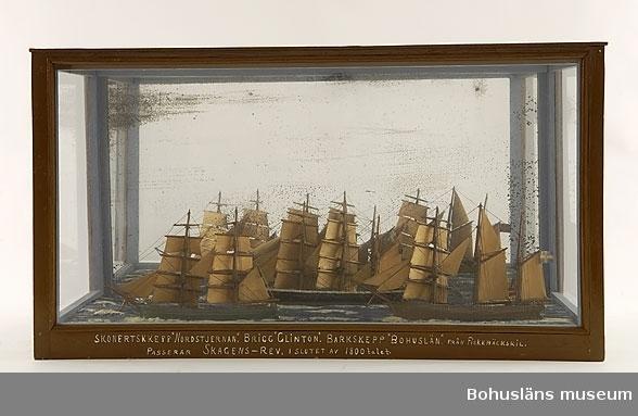 """Panorama med skonertskeppet Nordstjernan, briggen Clinton, barkskeppet Bohuslän och fyrskeppet Skagens rev.  Modellen tillverkad av kapten John Emil Olsson (1880 - 1950), Fiskebäckskil på Skaftö i Lysekils kommun på 1940-talet. Trä, metall, lintråd, glas, spegelglas, gips, målat med oljefärg.  Fartygsmodeller höjd 14 cm, längd 27 cm, bredd 3,5 cm.  Monterns mått 71 x 33 x 39 cm. Okänd skala. Vattenlinjemodeller av fyra fartyg, från vänster Clinton målad grön, Bohuslän målad svart, Norstjernan brun och Skagens rev är röd. Stående och löpande rigg, segel av snidat trä och unionsflaggan hissad på mesanmasten. Däckshus och lastluckor. Monterade på en utskuren rektangulär träplatta med modellerad och målad gipssjö, placerad i en monter mot en spegelbakgrund.  Framtill på modellens långsida står textat med vita tryckbokstäver:  SKONERTSKEPP """"NORDSTJERNAN"""". BRIGG """"CLINTON"""". BARKSKEPP """"BOHUSLÄN"""" FRÅN FISKEBÄCKSKIL. PASSERAR SKAGENS-REV I SLUTET AV 1800-talet.   Ur handskrivna katalogen 1957-1958: Tre skepp passerar Skagens rev i slutet på 1800-talet. Skonertskeppet Nordstjernan, Briggen Clinton, Barkskeppet Bohuslän. Modellerna i glasmonter. Hela.  På monterns baksida är monterat spegelglas. Som skydd bakom glaset sitter en del av ett äldre sjökort över """"Kerrera Channels & c. to Oban"""" samt """"Stornoway Harbour"""" - den tryckta sidan är gömd och dess baksida är blåmålad. Från kapten Olssons saml., Fiskebäckskil."""