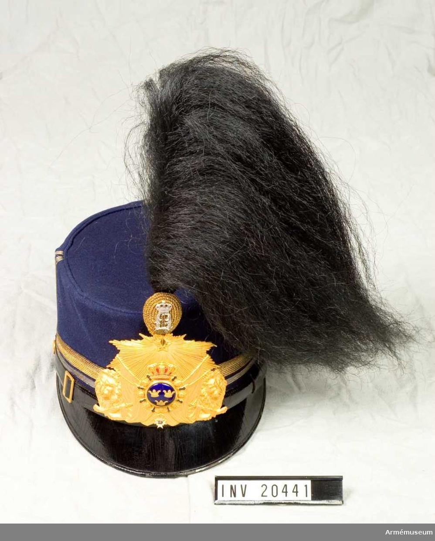 """Grupp C I. Ur uniformering för officer Hallands regemente. Består av vapenrockar, långbyxor, kappor, mössor, päls, handskar, ridstövlar. Av mörkblått, ev. svart, diagonaltyg. Knappar guld.  Anm. """"Paraden"""", dvs plåt och plym för mössan (inf) och epåletter (i st. f. axelklaffar) försvann 1932-01-01. Därefter är stor högtidsdräkt m/ä: vapenrock m axelklaffar, skärp m/1819, långbyxor m hällor, resårkängor, vita handskar. Buren av givarinnans make Uno Lindberg."""