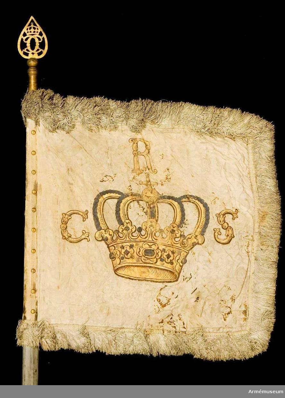 Duk: Tillverkad av dubbel, vit sidendamast. Mellanfoder av linnelärft. Duken fäst med fyra rader tennlikor på ett vitt band.  Mönster:  Fransk lilja inskriven i blomma. Mönsterrapport: Höjden ej synlig.  Dekor: Målad lika på båda sidor stor, sluten kunglig krona, h 265 mm och b 285 mm, i guld med silverpärlor (numera mycket oxiderade) på kronbyglarna samt på sidorna och över kronan C R S i guld, allt skuggat i mörkt brunt.  Frans: Dubbel, tillverkad av vitt silke.  Stång: Tillverkad av trä, kannelerad, gråmålad, avsågad. Löpande bärring (kraftig). Spets av förgylld mässing med spegel C krönt med sluten krona.