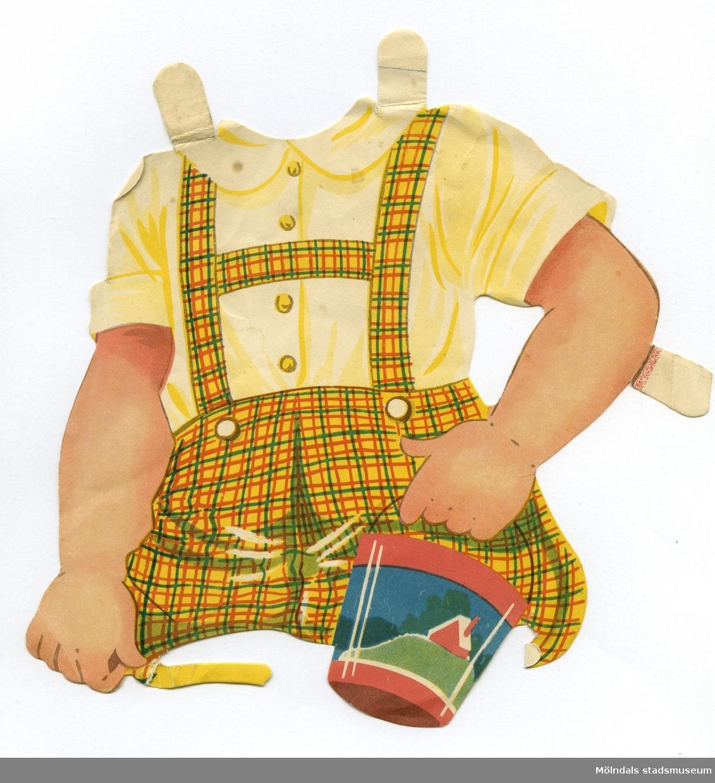 """Plagg till större pappersdocka, från 1950-talet. Kläderna är märkta """"Pelle"""" på baksidan - dockans namn. Själva dockan saknas dock. Garderoben består av pojkkläder; kortbyxor med skjorta för lek och skola, samt en brun rock."""