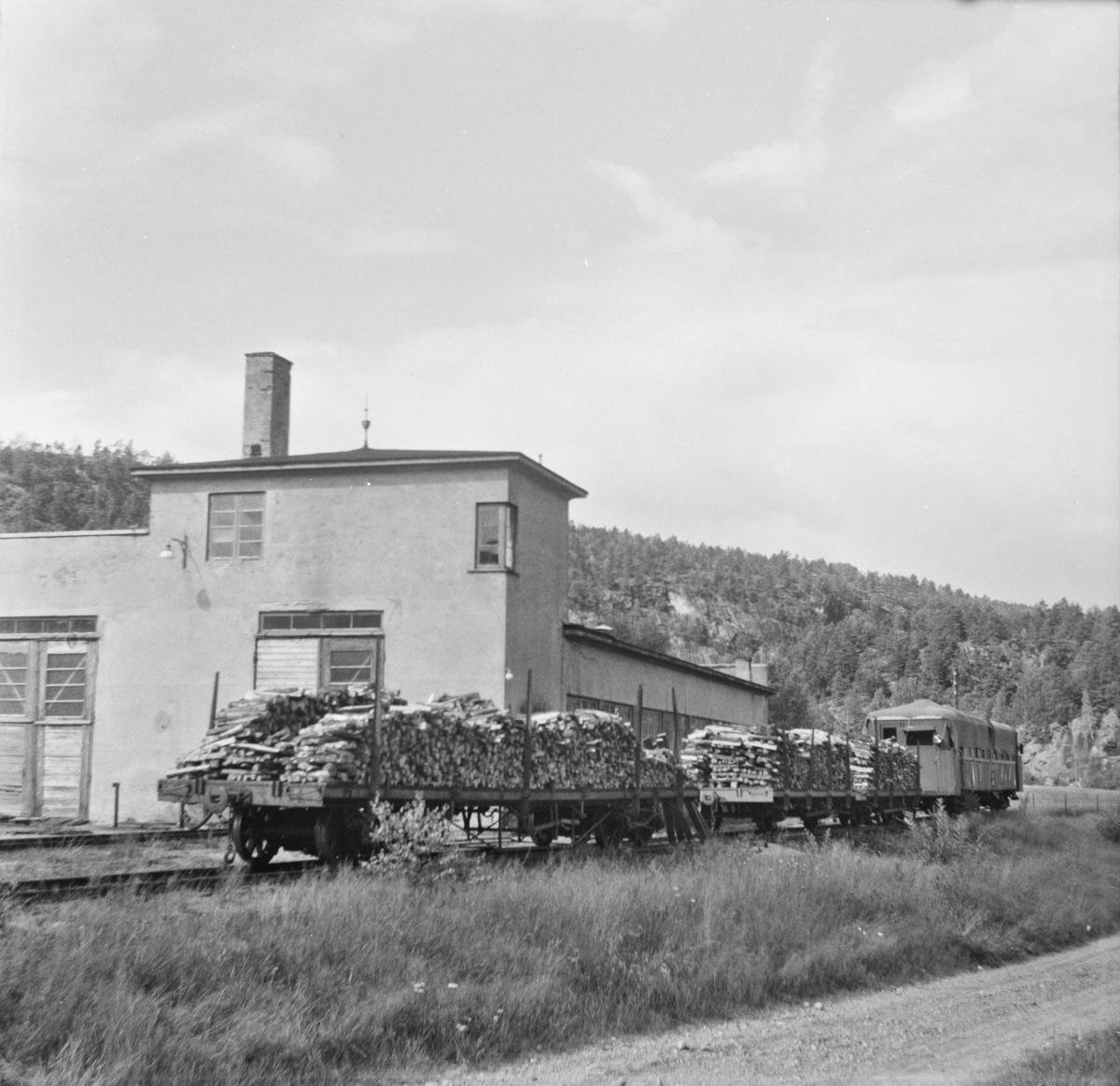 Godsvogner lastet med ved utenfor Setesdalsbanens verksted på Grovane. Bakerst motorvogn Bmbo 2674 under pressenning.