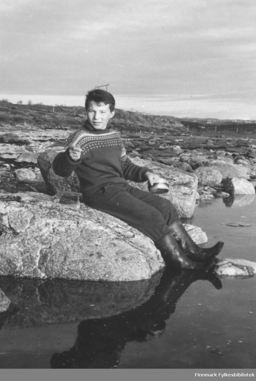 Torbjørn Nymo fotografert sittende i fjæra i Brennelv mens han fisker med en kasteboks.