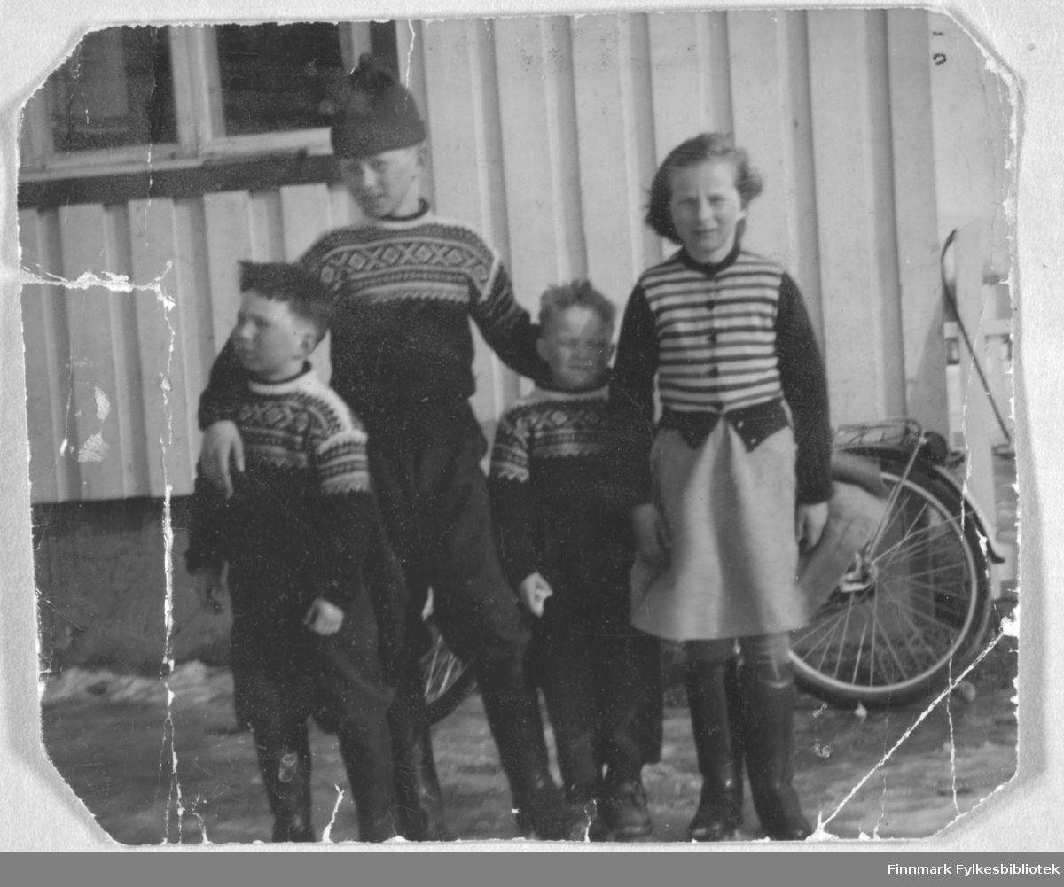 Fire barn fotografert utenfor et hus. De er fra venstre: Torbjørn, Ragnvald, Kjell og Ingrid, alle med Nymo til etternavn. Stedet er ukjent.