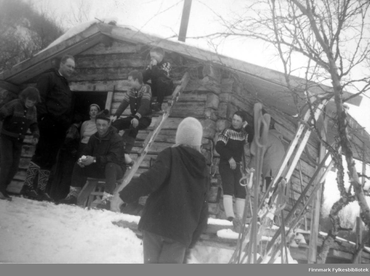 En liten gruppe mennesker utenfor en hytte. Personene er ukjent, men hytta kan være i Rochi i Porsanger.