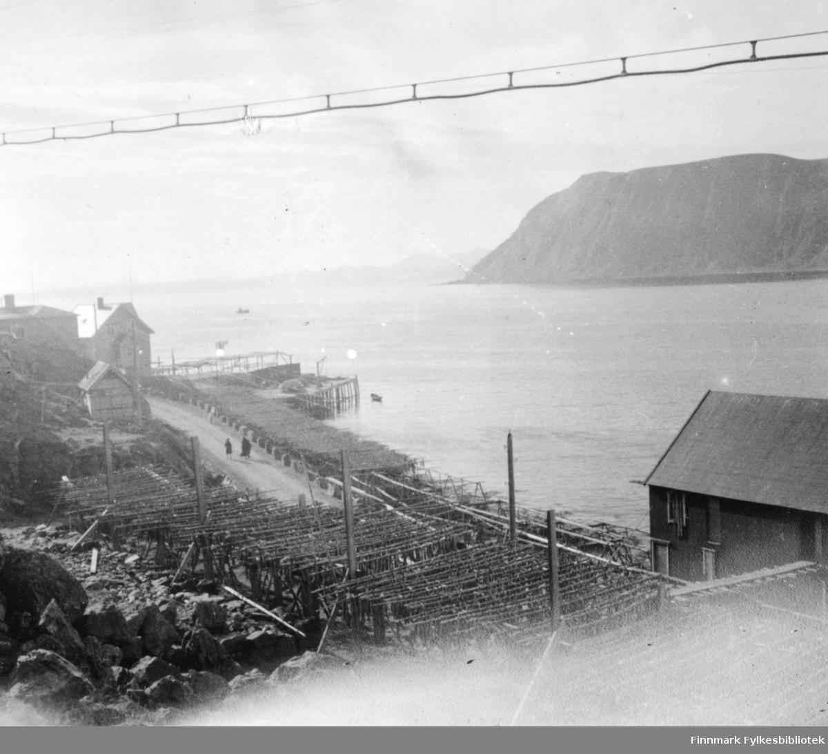 Landskapsbilde fotografert fra Honningsvåg. Foran på bildet fiskehjeller med fisk, noen bebyggelser og kai. Det gå to kvinner på grusveg bortover i bildet. Bildet er et stereobilde.  .