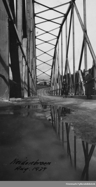 Bro over Neidenelva fotografert i august 1939. To ukjente presoner står på broa, en kvinne og en mann