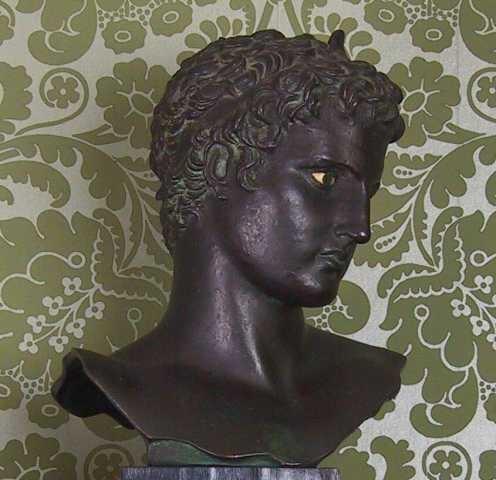 Skulpturhode i bronse. Avskjæring over skuldrene med bølgende kontur. Hodet høyrevendt, krøllet hår med pannebånd,  sorte øyne med hvitt øyeeple.