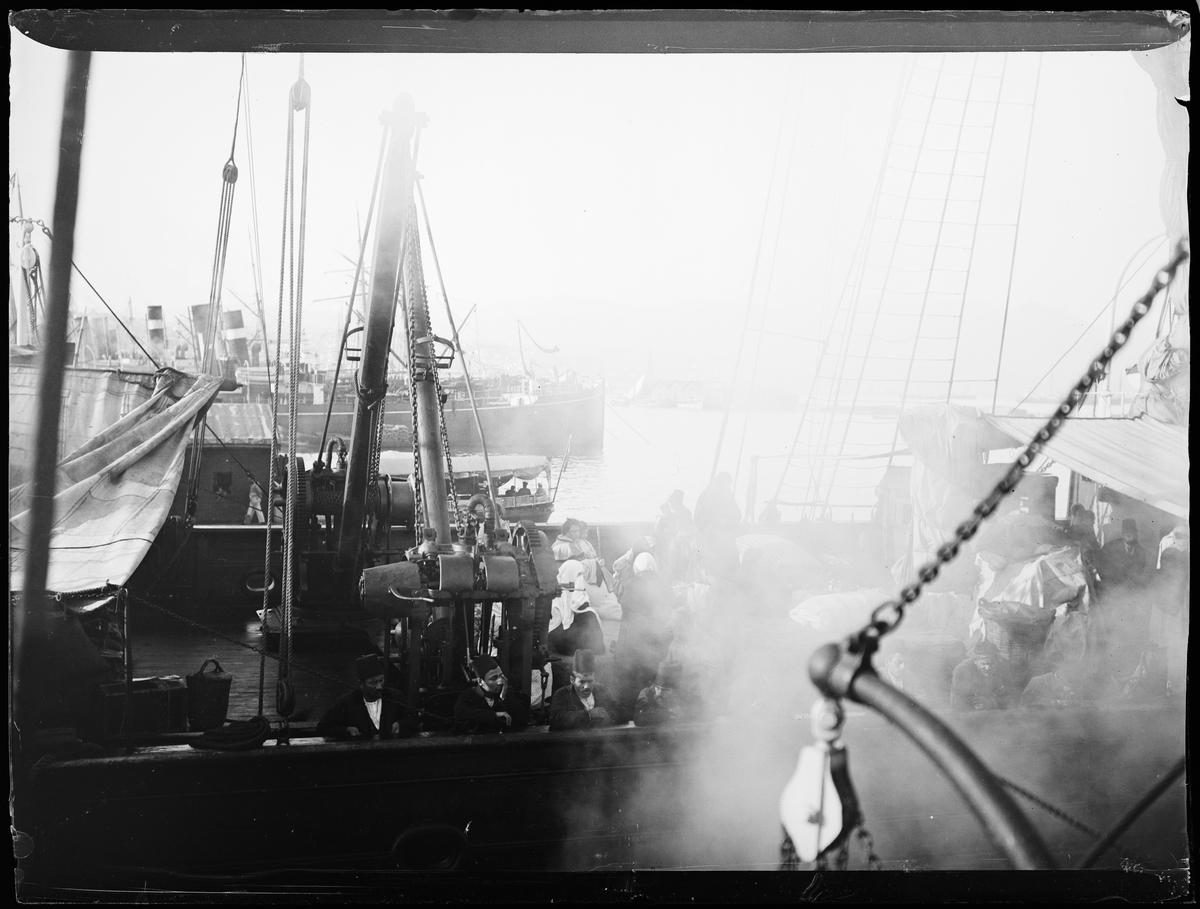 Mennesker på en båt som ligger i havn. Damp over halve bildet. Konstantinopel / Istanbul eller Jaffa.