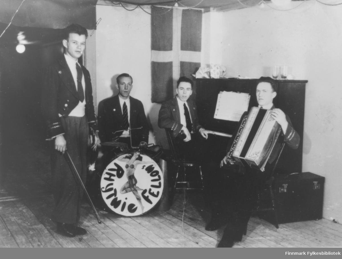 Bilde av 'Rhytmie Fellows' fra Kirkenes. Det står ingen dato på bildet. Fire menn med fiolin, trommer, piano og trekkspill. I bakgrunnen henger et flagg. Det må være dansk, svensk, eller finsk. Gruppen er kledt i dress.