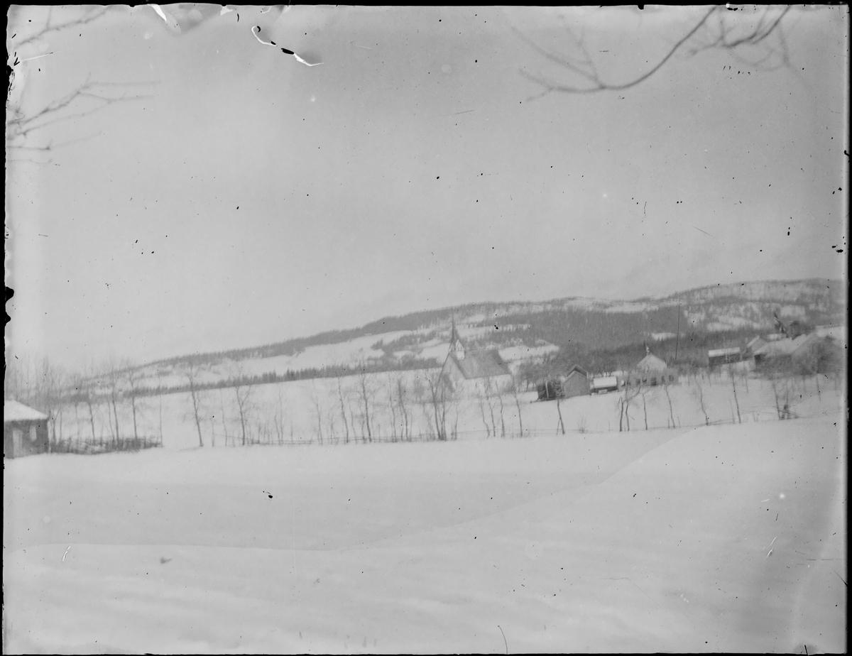 Vinterlandskap med Stiklestad kirke og annen bebyggelse fra avstand.