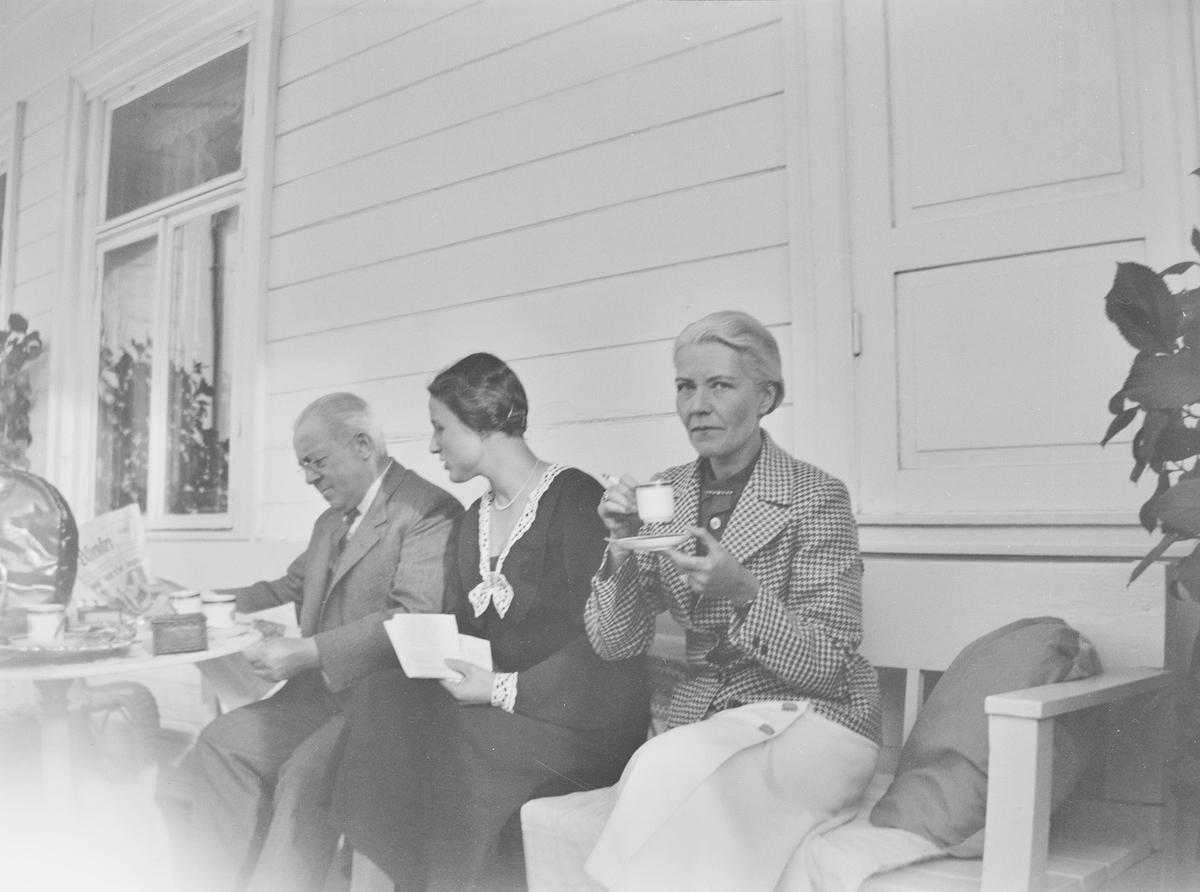 En mann, Christian Pierre Mathiesen, sitter sammen med to damer på en uteplass ved inngangspartiet til hovedhuset. De snakker, leser post og aviser samt drikker kaffe og/eller te.