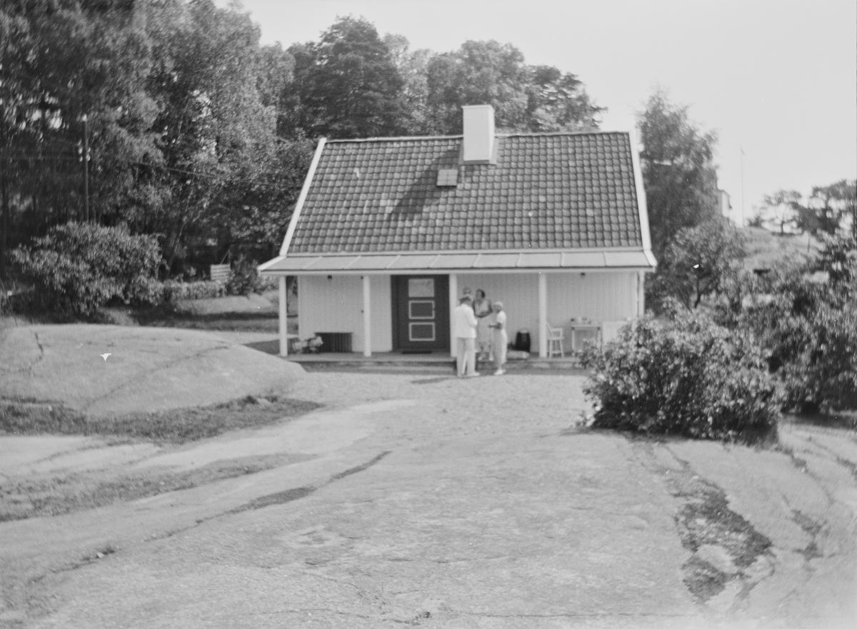 Et hus er bygget på et berg med trær og busker rundt. Fire personer, kledd i sommerklær, står sammen foran huset.