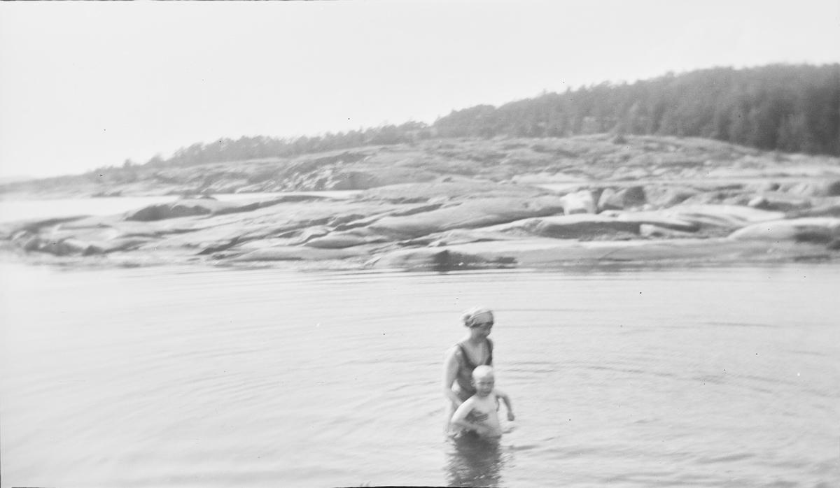 En kvinne står i vannet og holder en gutt under armene, som hjelp til å lære å svømme rygg. I bakgrunnen svaberg og skog.