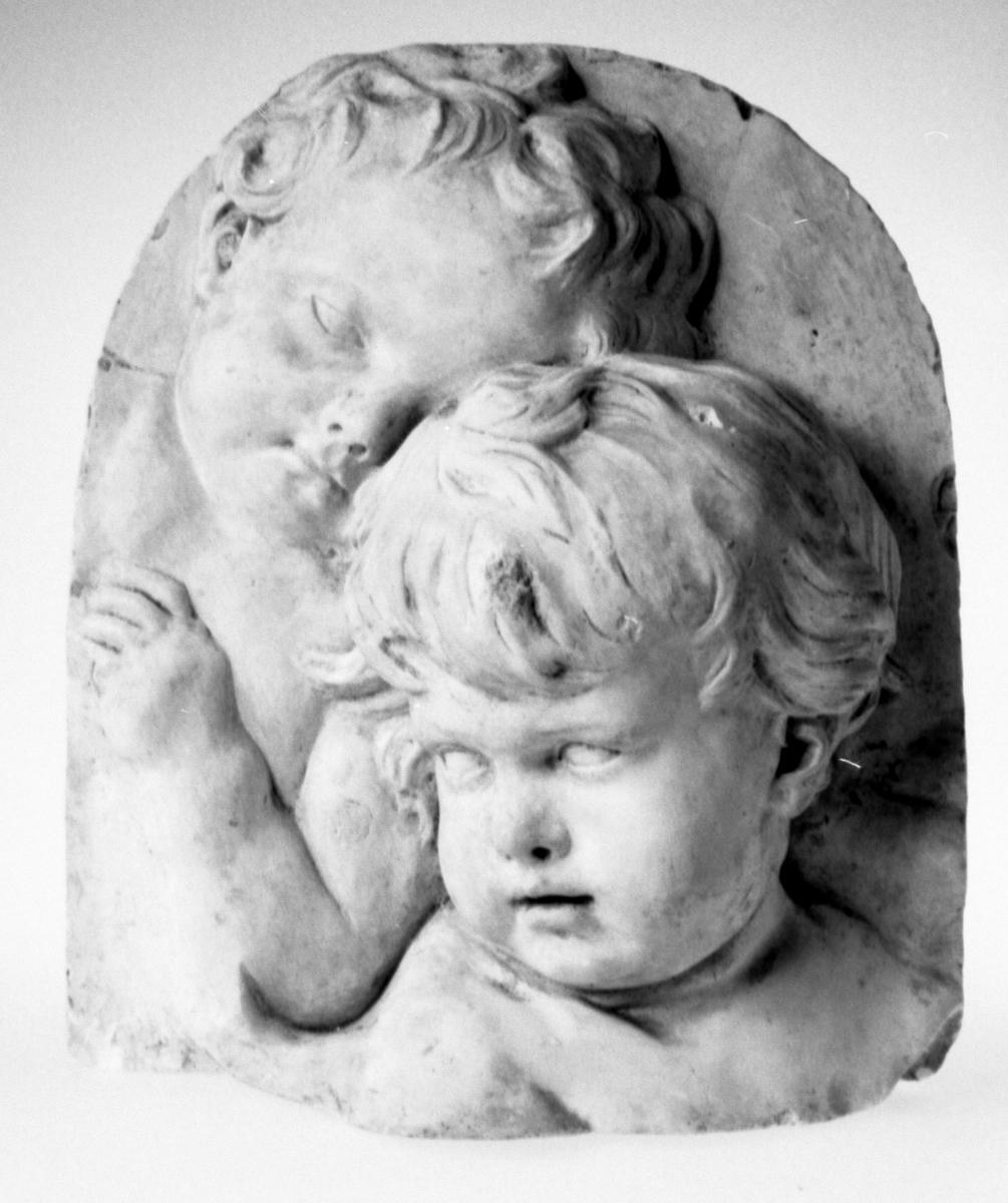 Byste av 2 barn, høyt relieff m. rundet avslutn. øverst, d.e. barnet legger hodet på d. annets isse.