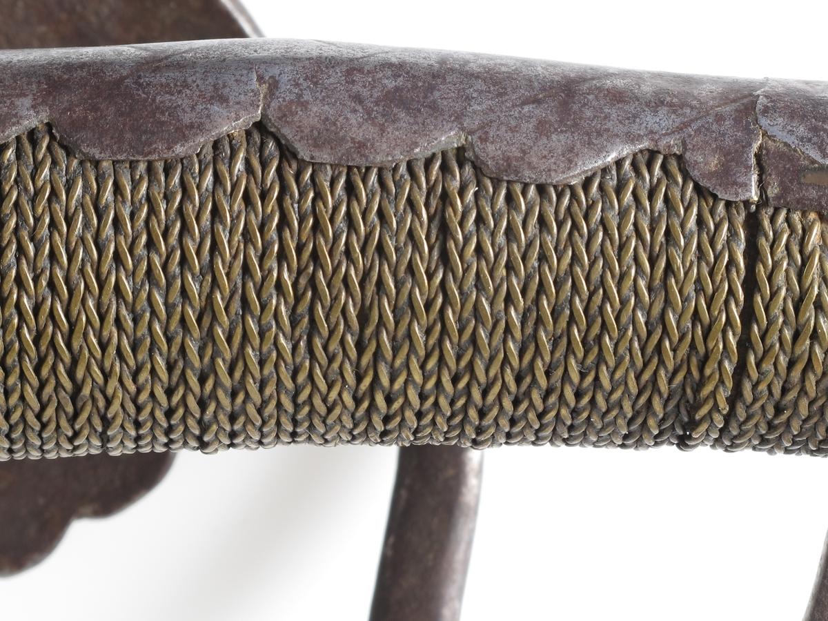 Kårde med håndkurv. Rett bred klinge med stort dobbeltmonogram F 4 inngravert øverst på begge  sider av klingen. Rett utstående parerstang, i den ene side bøyd opp i rett vinkel til beslaget øverst på skaftet,  som er omviklet med   flettet   jern  tråd og med toppbeslag som fortsetter nedover hele skaftet  (som et langt blad) med tunget kontur. Håndkurven har form  som et stort skjell, tvers overfor dette en oval ring med et   skjell  som bunn, tommelholder.  Tilstand: rusten.