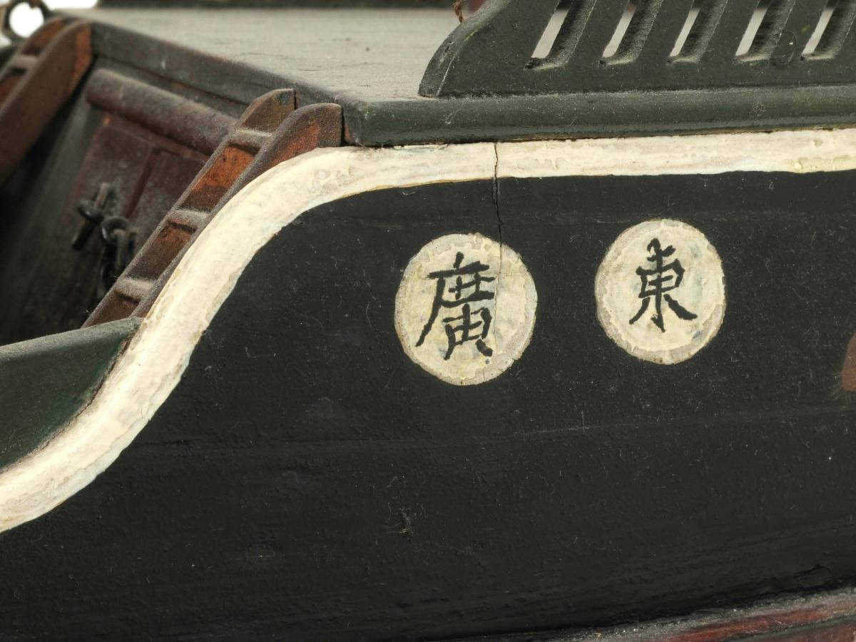 Modell av en djunk fra Kina, av tre; seil av flettet sivmatte.   Djunken har tre master, alle med seil. Okerfarget under  vannlinjen,  sort over, dekk og esing grønn, ruff oker. De to øverste  bordgangene videreføres og krummes oppe ved stevnen, som har et øye på hver  side. Trappeforskyvning akterut, det ytterste med   utskjæringer?  Delvis gjennombrutt. På hver båtside bakerst er det to  skrifttegn.  På poppen står en livbåt. En tilhørende åre, tre. L. 58.    Tilstand: god, bortsett fra seilene som er noe medtatte.  februar 1914.