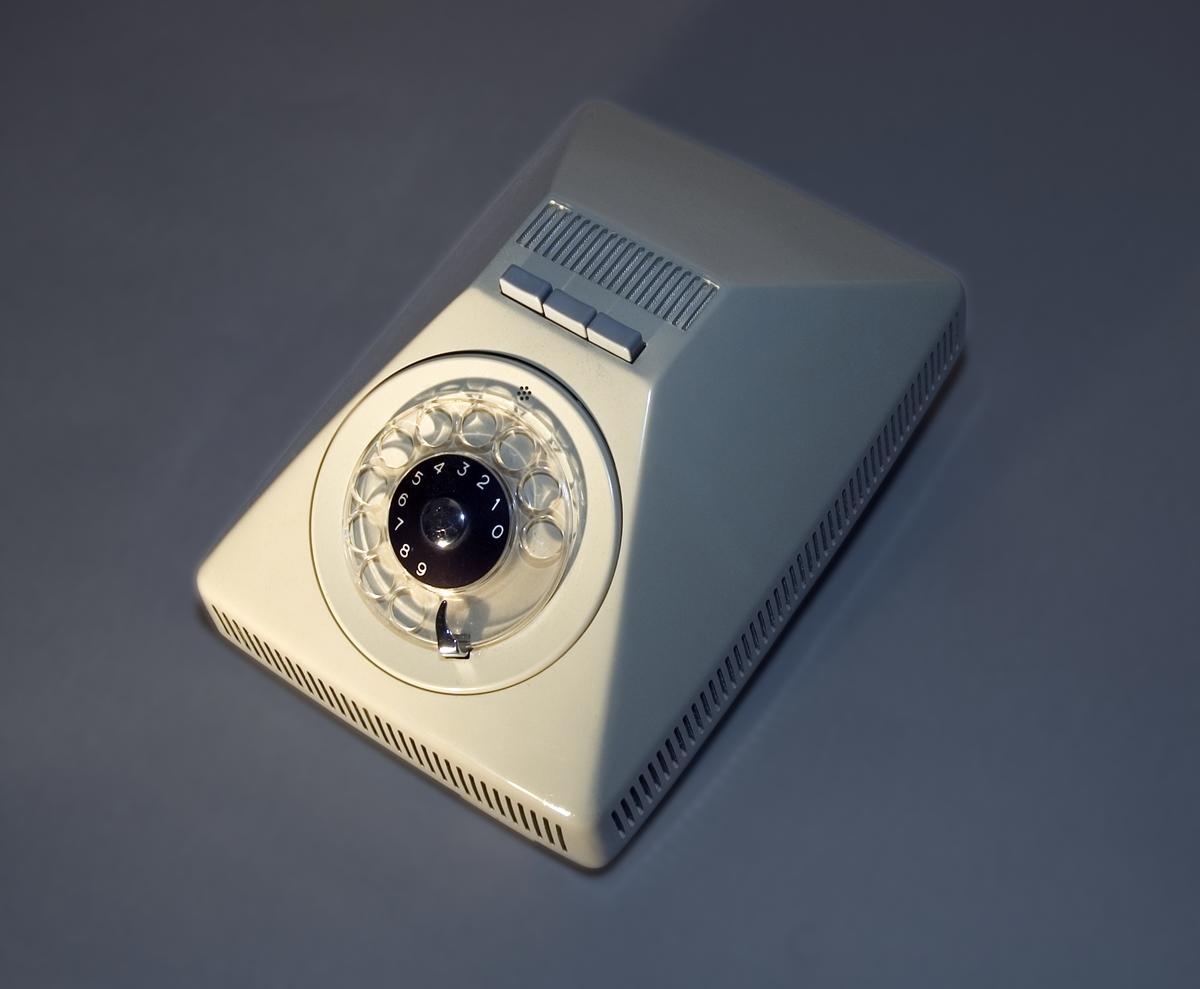 Föremålet består av en kombination av högtalartelefon och enstycksapparat. Högtalande telefonapparat Ericovox för AT-system, huvudapparat, anknytning till abonnentväxel och sidoapparat. Bordsmodell av grå termoplast med fingerskiva, inbyggd högtalare och mikrofon, glimlampa och tre tryckknappar för inkoppling av linjen, justering av högtalarvolymen och temporär avstängning av mikrofonen. Ericovox saknar mikrotelefon och används alltid tillsammans med en vanlig mikrotelefonförsedd apparat, vanligtvis en Ericofon.  Telefonapparat Ericofon, även kallad Kobra, för AT-system, sidoapparat till Ericovox. Bordapparat modell m57 av termoplast utan inbyggd ringklocka och med alla komponenter sammansatta till en enhet. Fingerskivan av plast är försänkt i apparatfoten. Klykfunktionen är realiserad med en knapp som skjuter ut ur fingerskivans centrum och påverkas av apparatens tyngd.