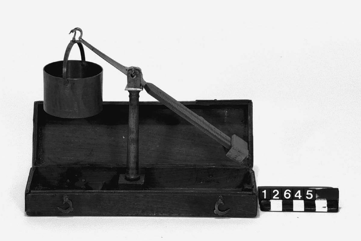 """Enarmad isärtagbar balansvåg, spannmålsprovare, av mässing med cylindrisk vågskål. I fodral av trä. Stämplad: """"I B 5"""". Skala """"5 P - 10 - 6 - 18 (P)"""". 7 enheter=23 gr.=qvintin. Vågen visar vikten av en tunna spannmål, då vågskålen är full och struken."""