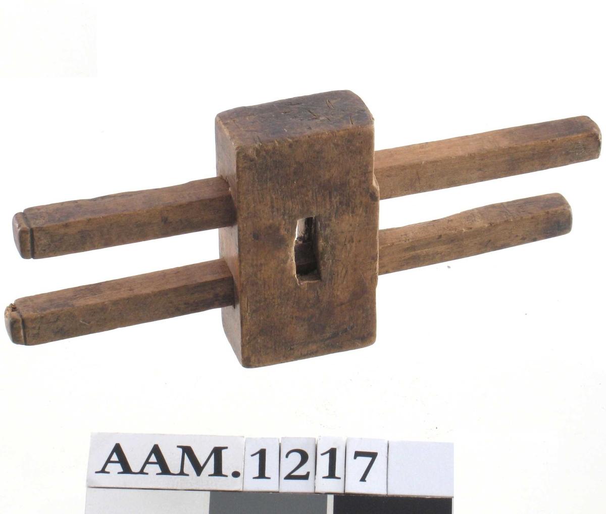 Strekmåt av bjerk. Kloss m. 2 forskyvbare stenger, hver m. en  liten jern spiss ved enden. Midt i klossen et gjennomgående hull.