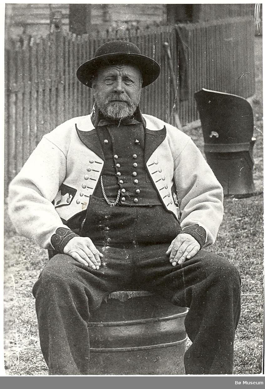 Halvor Knutson Nordbø i gråkufte, sit i kubbestol