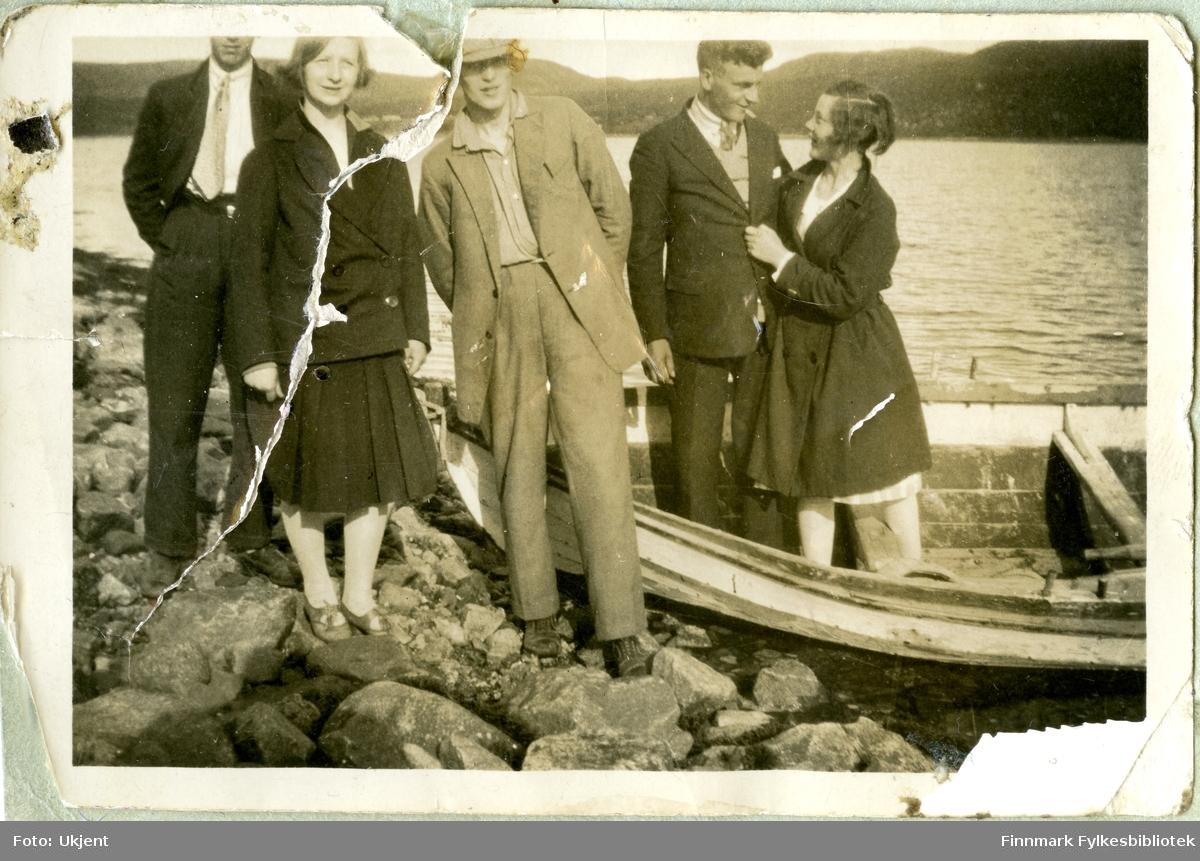 Gruppeportrett av kvinner og menn. De fleste på bildet er ukjente, men mannen som står i båten er Petter Aule. Mennene er kledd i jakker, bukser, slips og hatter. Kvinnene i kjoler, strømpebukser, sko og jakker. Gruppen står på steiner. Bildet er tatt i Jarfjordbotn. De andre avbildete personene kan være fra Vardø.