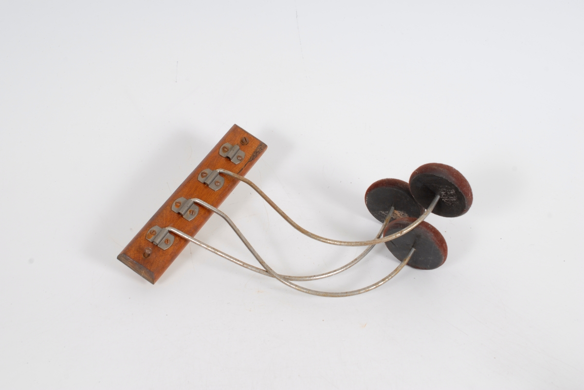 """Form: et rektangulært trestykke med bøyde metallarmer i fester, hver arm er svingbar og har en tre""""pute"""" til å henge hatten på"""