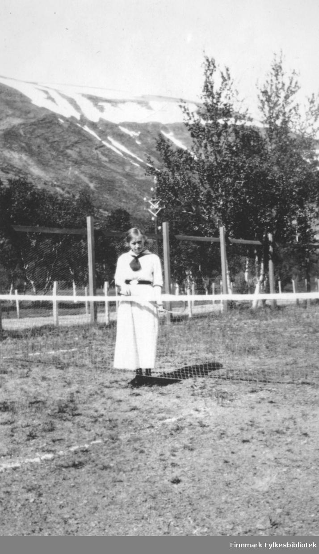 """""""Verdens nordligste tennisplass juli 1917"""" står det i albumet som tilhørte Hans Gabrielsen. En ung pike kledd i hvite tennisklær står ved et tennisnett med en tennisracket i hendene. I bakgrunnen sees en grusvei og bjørkeskog, i det fjerne ser vi et fjell med snøflekker. Tennisbanen er i Bonakas, i nærheten av Birkelund. Damen på bildet er Sigrid (Siggen) Winger (født Gabrielsen), altså Hans Gabrielsens søster. Sigrid (Siggen) Winger var senere blant annet kontorfullmektig ved statsministerens kontor (1956).  Hans Gabrielsen var jurist og senere også fylkesmann i Finnmark. Etter krigen var han aktivt med i gjenoppbyggingen av Finnmark."""