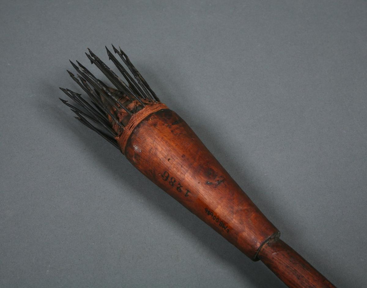 En stang med et dråpeformet hode som det er festet rette kroker med mothaker til.