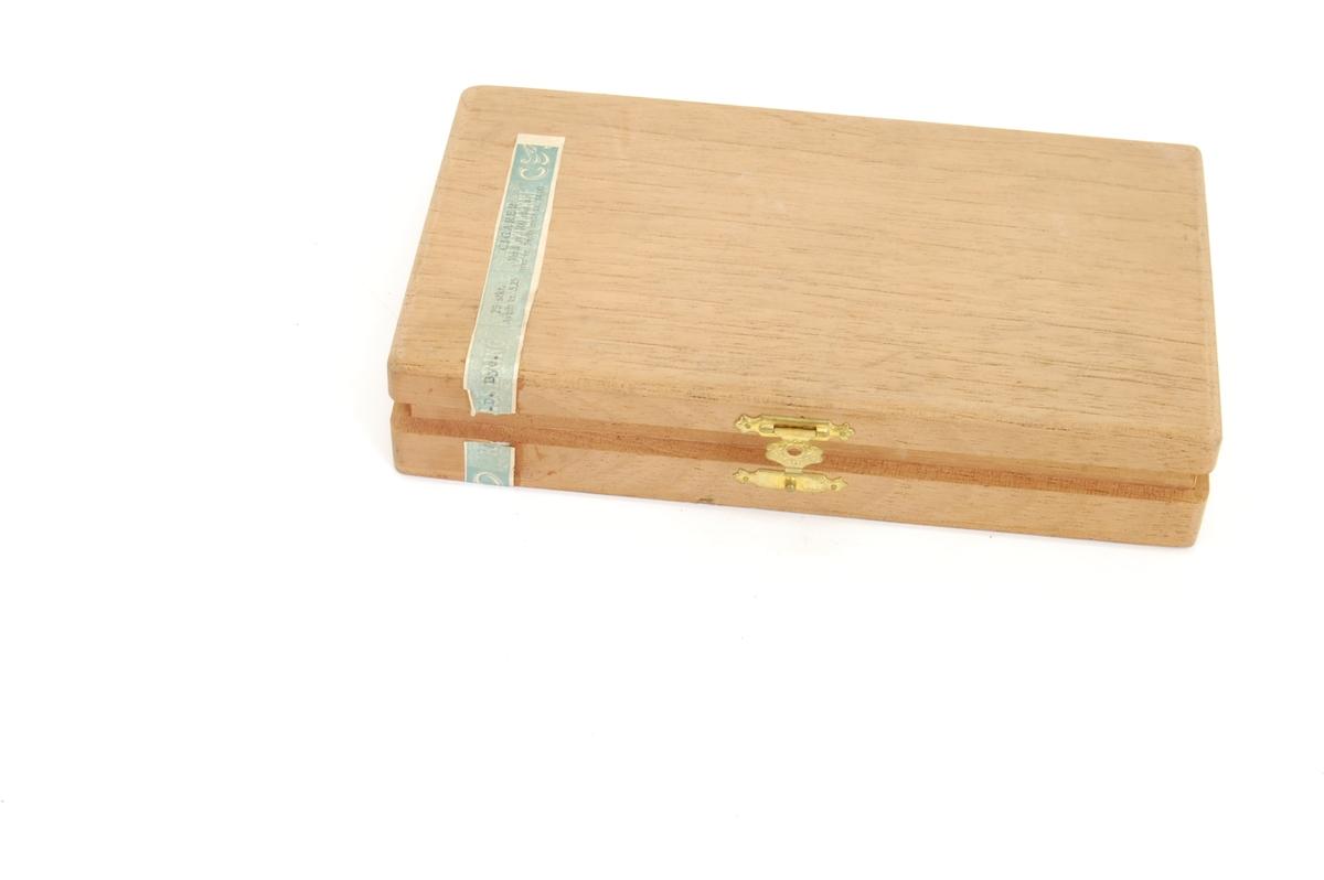 papirremse med skrift og akantuslignenede border, lås i messing med utstanset mønster og inngravert bord