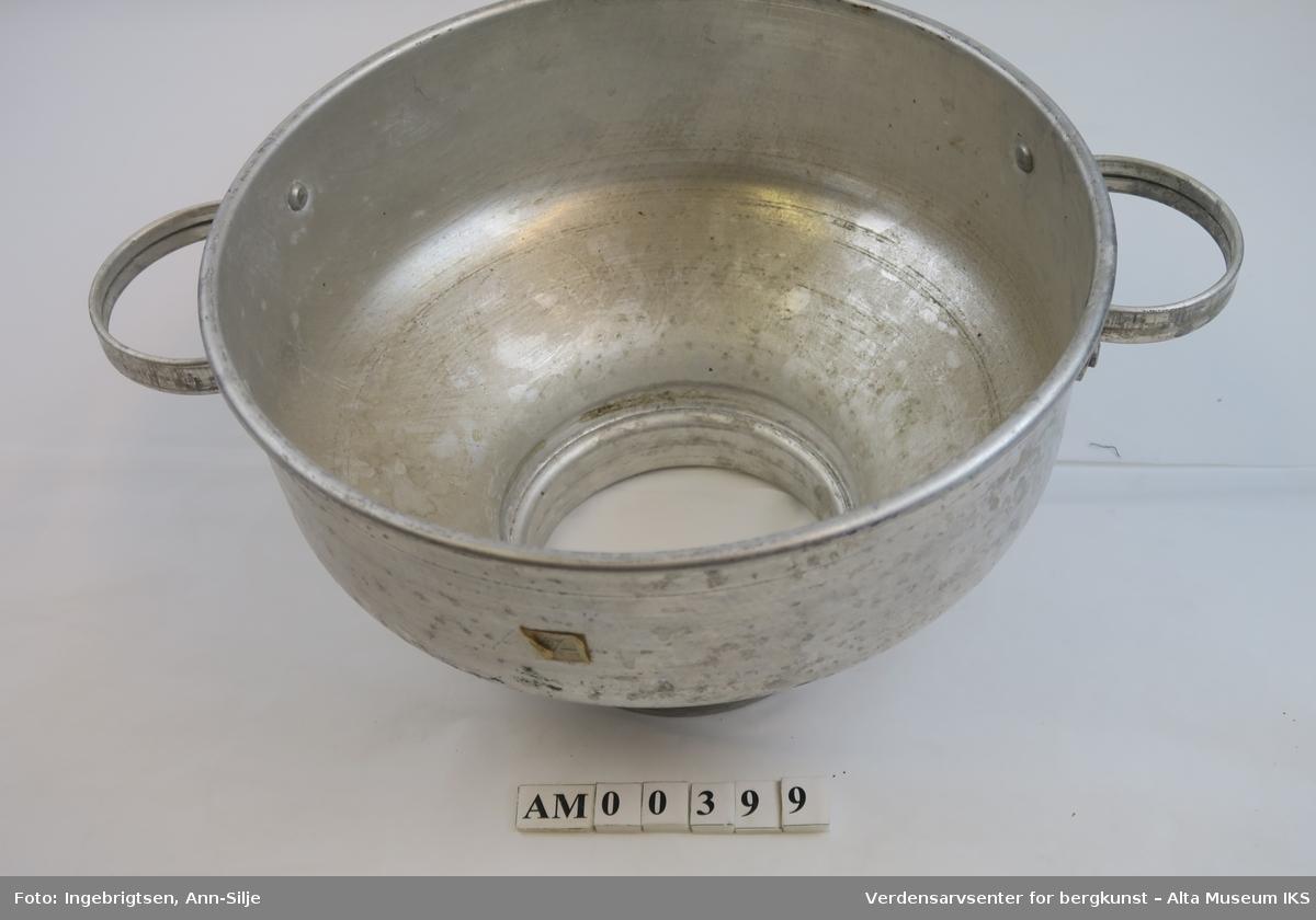 Rund melkesil med to buede håndtak på hver side. Diameteren nede er mindre enn åpningen.