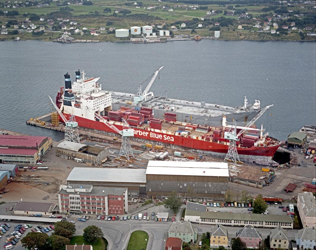 """Flyfoto H.M.V. Oversiktsfoto. Tankskipet """"Polyviking"""" fra Kristiansand ved kai. Frakteskipet Barber Blue Sea i dokk. Karmøy i bakgrunnen."""