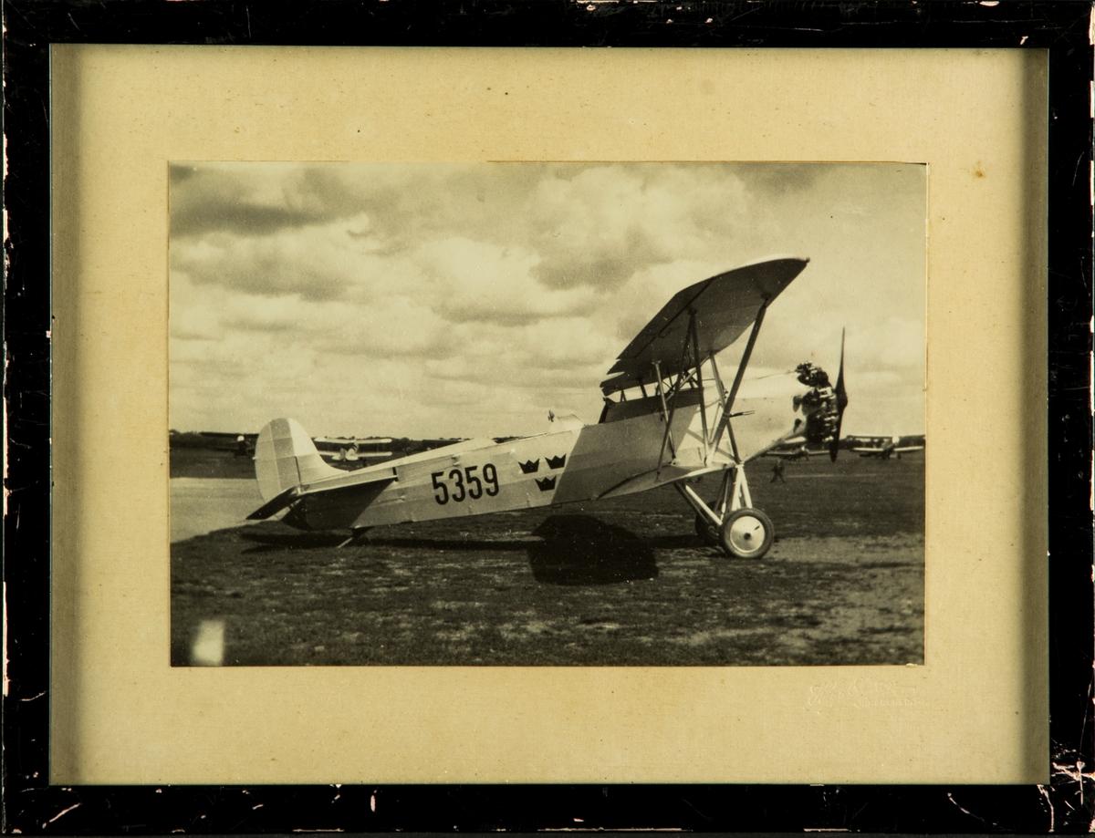 Jaktflygplan J 3 nummer 5359 tillhörande F 5 Krigsflygskolan står på flygfält. Inramat foto.