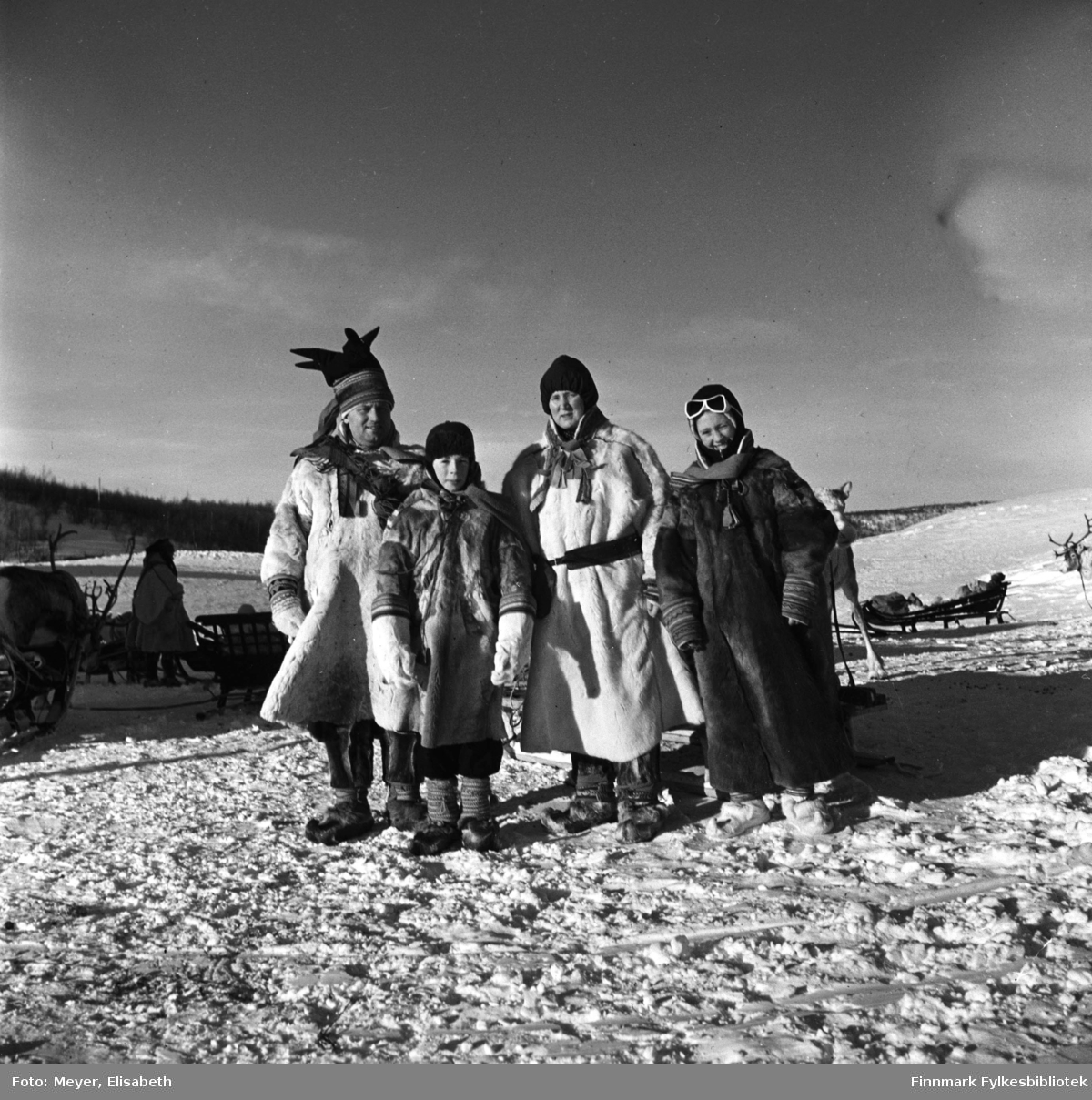 Turister kledd i pesk besøker Statens fjellstue, Suolovuopm i Maze. Personer ukjente. Fotografert ved påsketider 1940. Suolovuopmi fjellstue ble etablert i 1843 og var den første som ble etablert i Finnmark. Etterspørselen etter overnattingssted i indre Finnmark kom da post og fogd skulle ut å reise. Fjellposten, som begynte i 1799 gikk fra Hammerfest til Haparanda om vinteren. Suolovuopmi Fjellstue ble brent under krigen i 1944 og ble så gjenoppbygd etter krigen - og er fortsatt i drift.